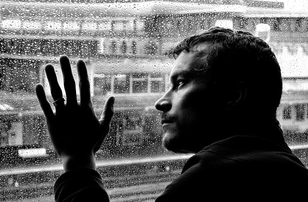 depressed adult male at rainy window