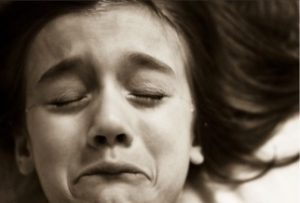 crying young girl suffering from addicted parent on spice