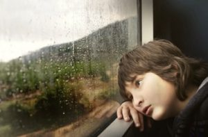 child longingly looking out window